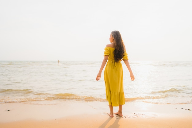 Portrait beautiful young asian woman walk on the beach and sea ocean with smile happy relax
