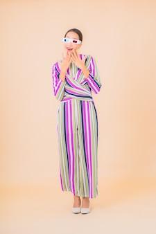 肖像画の美しい若いアジアの女性は、カラーで映画を見るために3d眼鏡を着用します