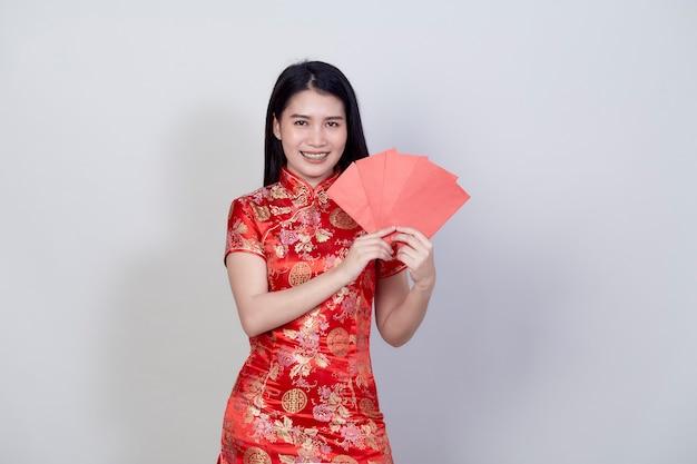 Портрет красивой молодой азиатской женщины в китайском платье с красным пакетом денежного подарка поздравления с новым годом 2021 года, изолированным на светло-сером фоне с копией пространства