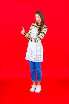 세로 아름 다운 젊은 아시아 여자 붉은 벽에 앞치마를 착용