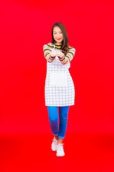 肖像画美しい若いアジアの女性は赤い壁にエプロンを着用