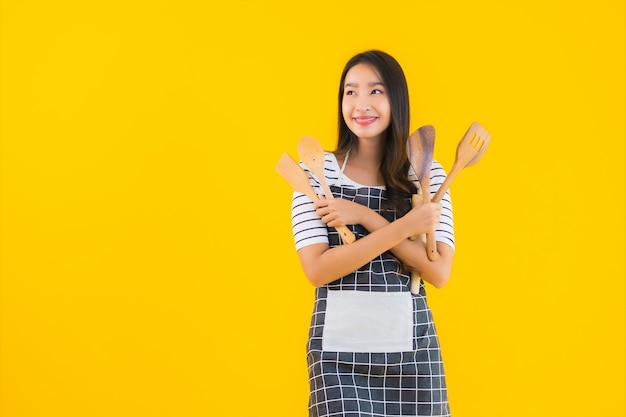 Portrait beautiful young asian woman  wear apron with black pan and spatula