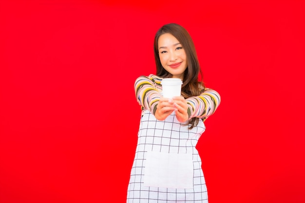 세로 아름 다운 젊은 아시아 여자 붉은 벽에 커피 컵과 앞치마를 착용