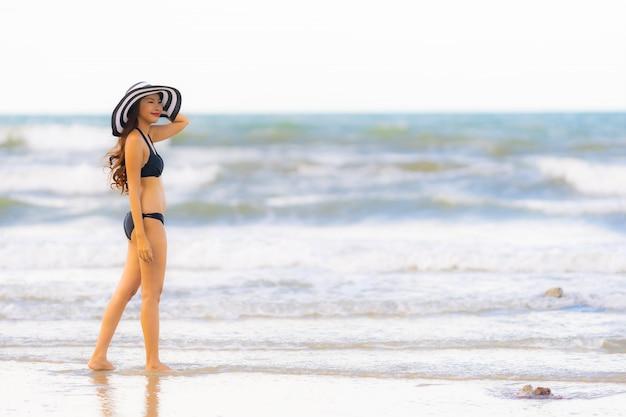 해변 바다 바다에 세로 아름 다운 젊은 아시아 여자 착용 비키니