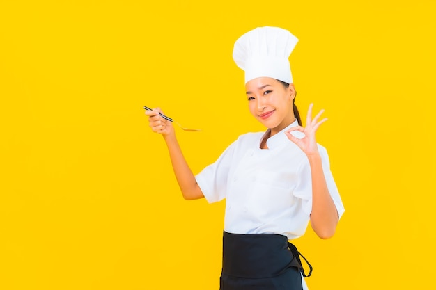 Portrait beautiful young asian woman wear chef or cook uniform with spoon and fork on yellow isolated background