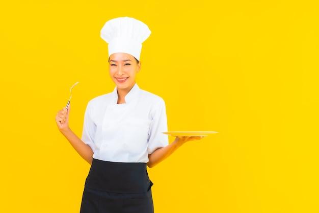 肖像画美しい若いアジアの女性は、シェフを着用するか、黄色の孤立した背景にスプーンとフォークで制服を調理します