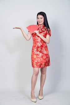 Portrait beautiful young asian woman wear a chinese dress  holding red packet monetary gift of congratulation greeting happy new year 2021isolated on light gray background with copy space