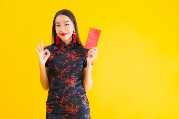 Bella giovane donna asiatica del ritratto indossa il vestito cinese con ang pao o la lettera rossa con contanti