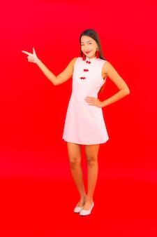 肖像画美しい若いアジアの女性は赤い壁に旧正月の服を着る