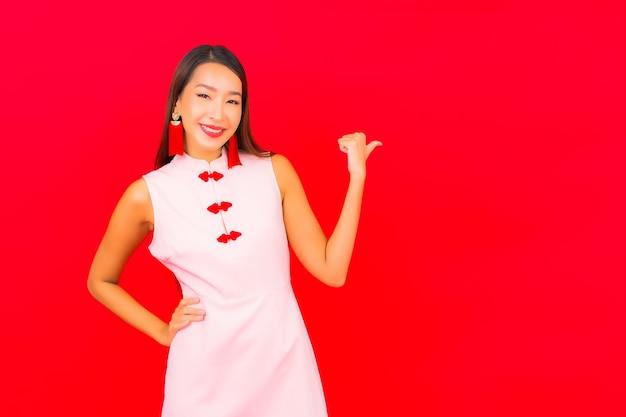 Женщина портрета красивая молодая азиатская носит одежду китайского нового года на красной стене