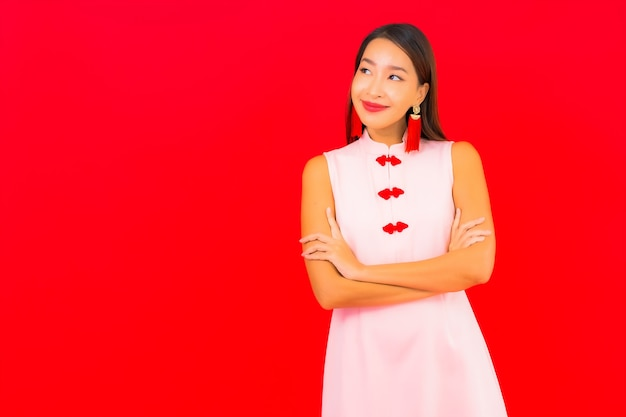 La bella giovane donna asiatica del ritratto indossa i vestiti cinesi del capodanno sulla parete rossa