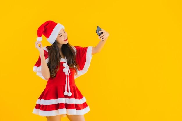 肖像画美しい若いアジアの女性はクリスマスの服を着て、帽子は携帯電話を使用します