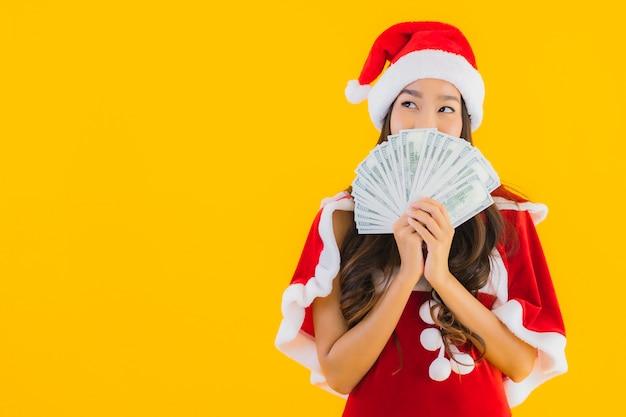 肖像画の美しい若いアジア女性はクリスマスの服と現金で帽子を着用します。