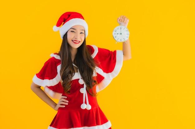 La bella giovane donna asiatica del ritratto indossa i vestiti di natale e l'orologio di esposizione del cappello