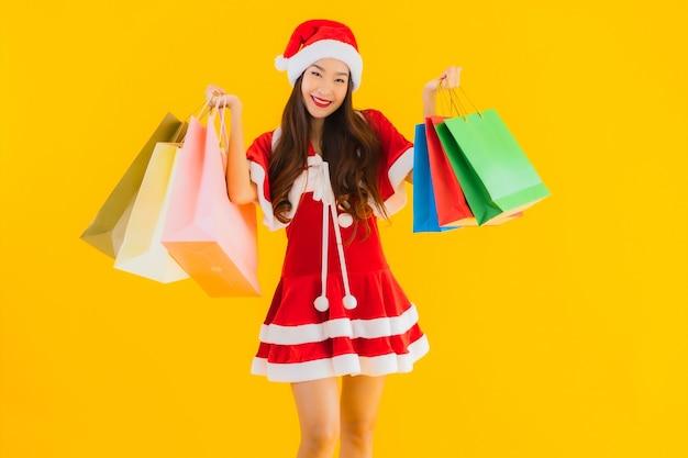 세로 아름 다운 젊은 아시아 여자는 쇼핑백의 많은 크리스마스 옷 모자를 착용