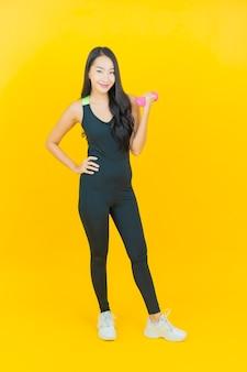 Обмундирование спортзала носки женщины портрета красивое молодое азиатское держа гантели