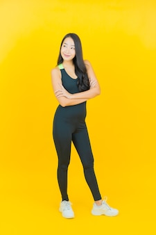 Portrait beautiful young asian woman wear gym outfit ready for exercise on yellow