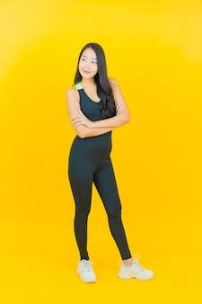 Обмундирование спортзала носки женщины портрета красивое молодое азиатское готовое для тренировки на желтом цвете