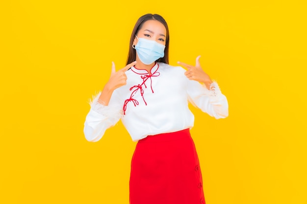Портрет красивой молодой азиатской женщины носит маску и использует спиртовой гель для защиты covid19 на желтом