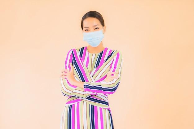 肖像画の美しい若いアジアの女性は、コロナウイルスまたはcovid19を保護するためのマスクを着用します
