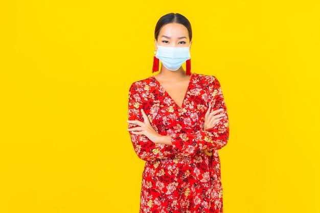 黄色の壁にコロナウイルスまたはcovid19を保護するための肖像画の美しい若いアジアの女性の着用マスク