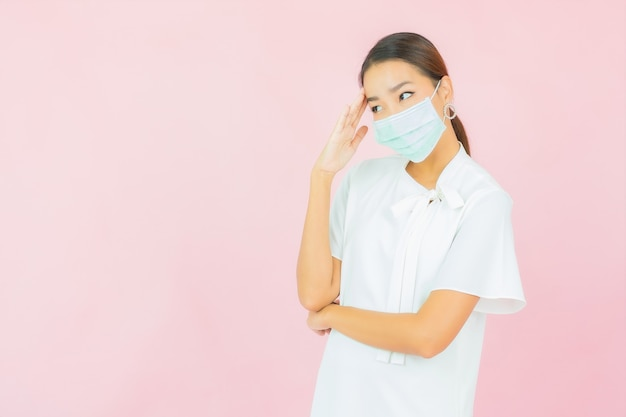 분홍색 벽에 covid19를 보호하기 위해 초상화 아름 다운 젊은 아시아 여자 착용 마스크
