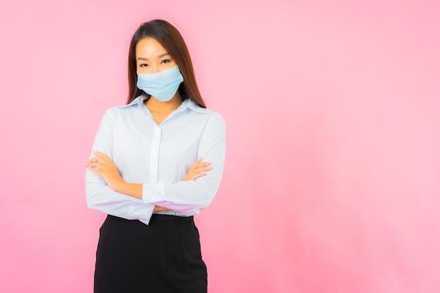 ピンクの壁にcovid19とコロナウイルスから保護するための肖像画の美しい若いアジアの女性の着用マスク