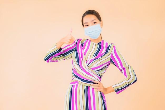La bella giovane donna asiatica del ritratto indossa la maschera per proteggere il virus corona o covid19 sul colore