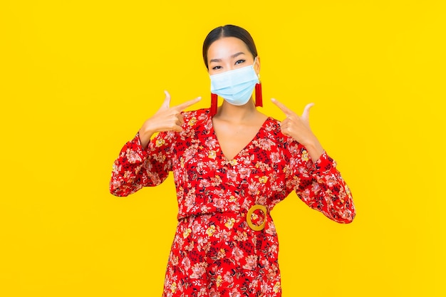 Portrait beautiful young asian woman wear mask for protect corona virus or covid19 on yellow wall
