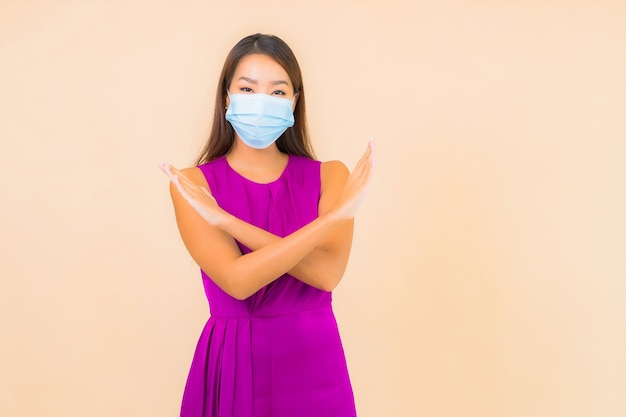 Portrait beautiful young asian woman wear mask for protect from covid19 or corona virus on color background