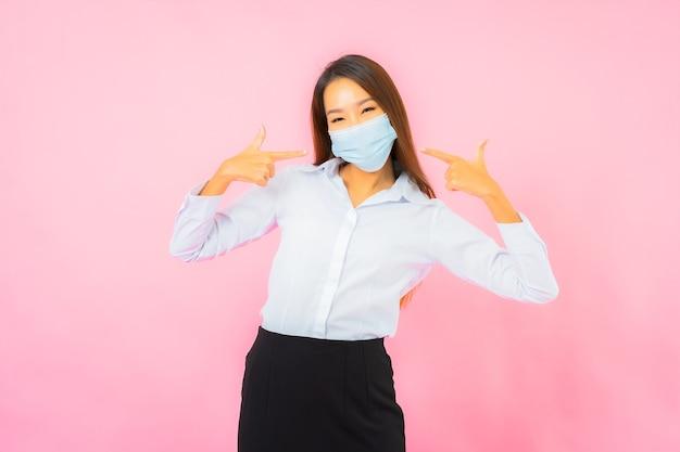 Ritratto bella giovane donna asiatica indossa una maschera per proteggersi da covid19 e coronavirus sul muro rosa