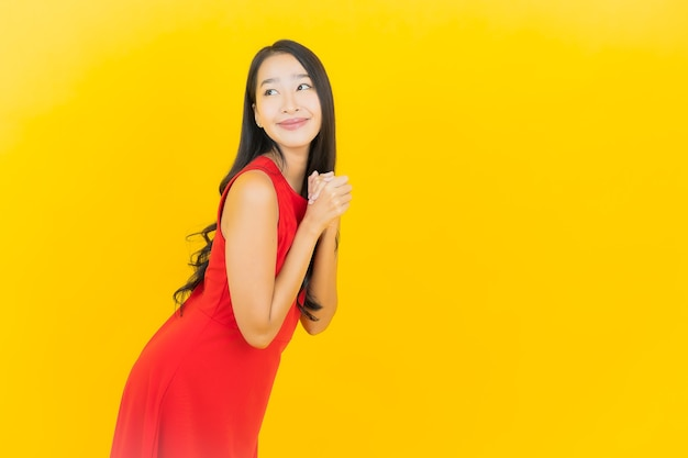 세로 아름 다운 젊은 아시아 여자 착용 빨간 드레스 미소 노란색 벽에 행동