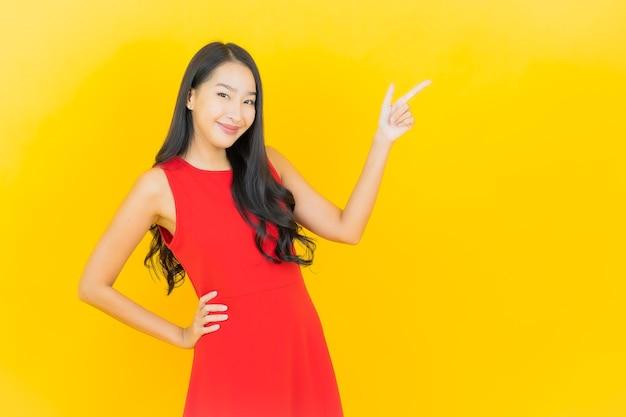 肖像画美しい若いアジアの女性は黄色の壁にアクションと赤いドレスの笑顔を着る