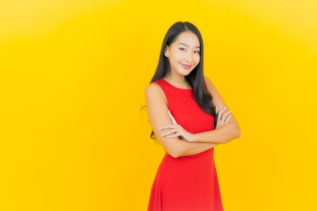Portrait beautiful young asian woman wear red dress smile with action on yellow wall