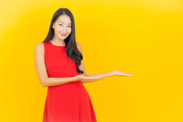 La bella giovane donna asiatica del ritratto indossa il sorriso rosso del vestito con l'azione sulla parete gialla