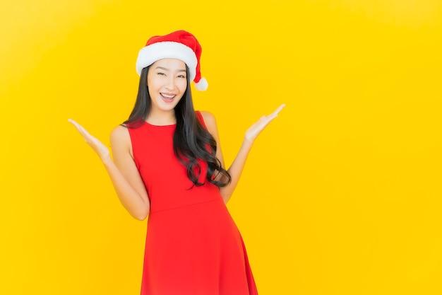 세로 아름 다운 젊은 아시아 여자는 노란색 벽에 산타 모자 또는 헤어 밴드를 착용