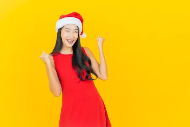 肖像画美しい若いアジアの女性は黄色の壁にサンタの帽子やヘアバンドを着用します