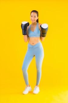 Спортивная одежда женщины портрета красивая молодая азиатская на желтом цвете