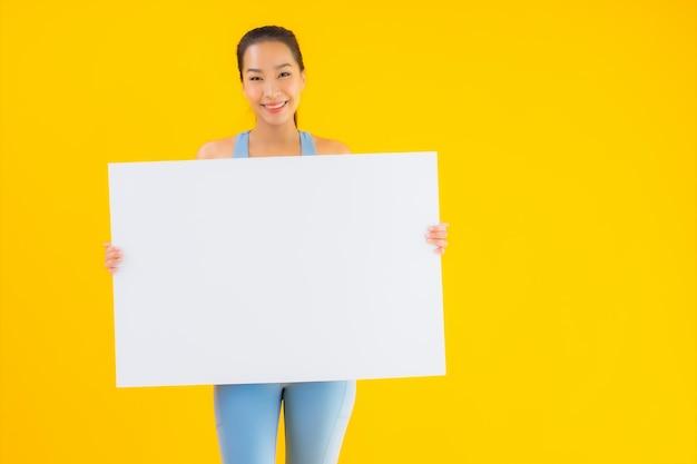 Portrait beautiful young asian woman wear sportwear show empty white billboard on yellow