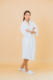 Portrait beautiful young asian woman wearing bathrobe with smile on beige