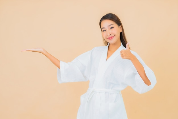 Халат красивой молодой азиатской женщины портрета нося с улыбкой на бежевом