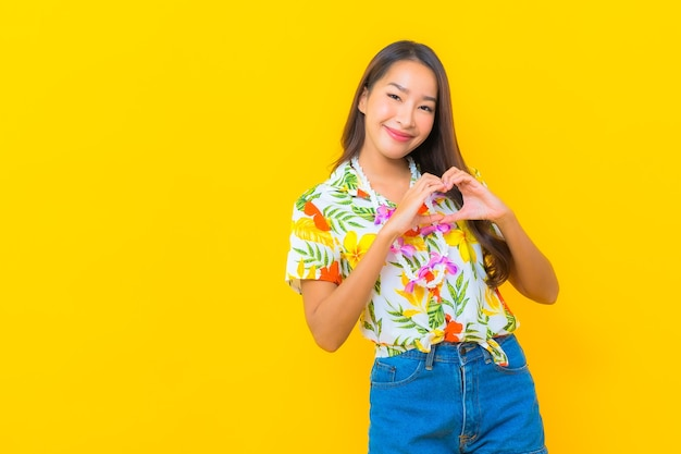Portrait of beautiful young asian woman wearing colorful shirt and making heart sign on yellow wall
