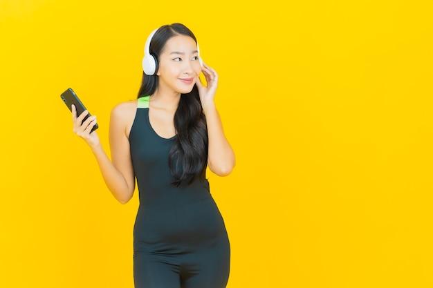 ヘッドフォンとスマートフォンでジムの衣装を着ている肖像画の美しい若いアジアの女性