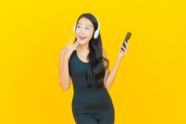 Обмундирование спортзала красивой молодой азиатской женщины портрета нося с наушниками и smartphone