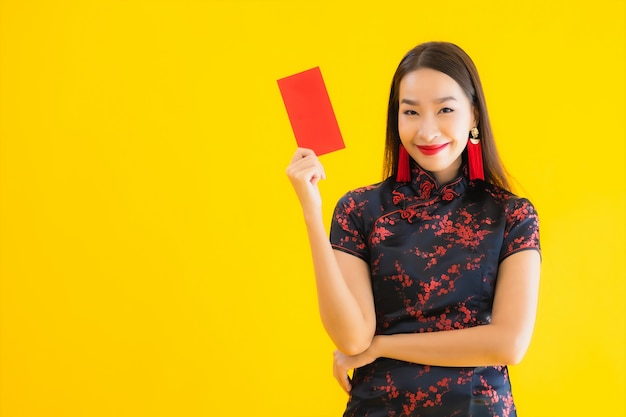 Portrait of beautiful young asian woman wears chinese dress and holds red letter