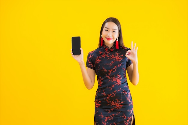 Portrait of beautiful young asian woman wears chinese dress and uses smartmobile phone