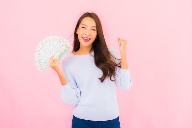 ピンク色の壁にたくさんの現金とお金を持つ肖像画の美しい若いアジアの女性
