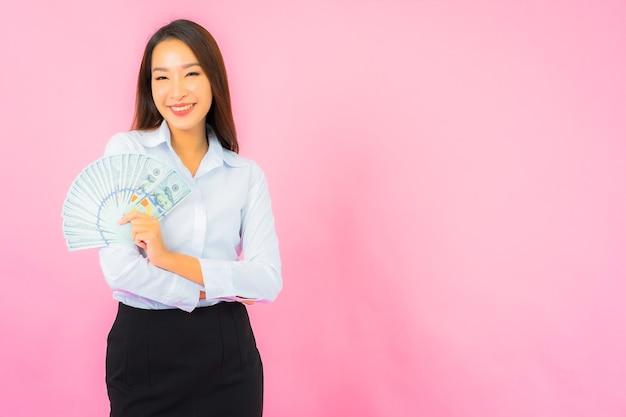 분홍색 벽에 많은 현금과 돈을 가진 아름다운 젊은 아시아 여성 초상화