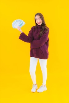 たくさんの現金とお金を持つ肖像画の美しい若いアジアの女性