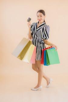 多くの買い物袋を持つ美しい若いアジア女性の肖像画